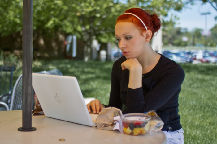 student sitting outside at table