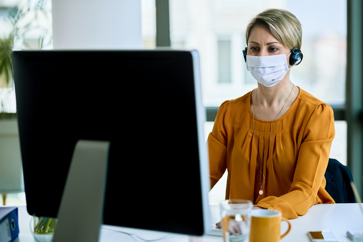Online learner in front of laptop wearing covid mask