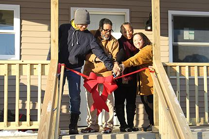 The Bond family cuts the ribbon on their new home.