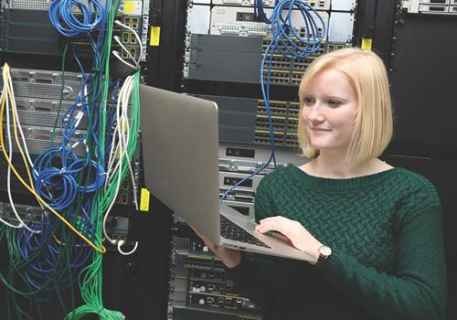 Female working on a computer in a computer server room