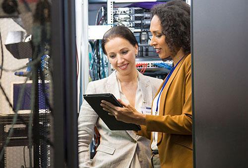 2 women viewing tablet in computer server room