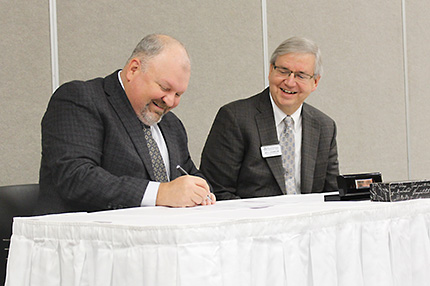Anthea Schroeder Local 669 Business Manager Brian Dunn (left) and WCC Vice President and Chief Financial Officer William Johnson sign the contract that extends the two parties' apprenticeship training program through 2022.