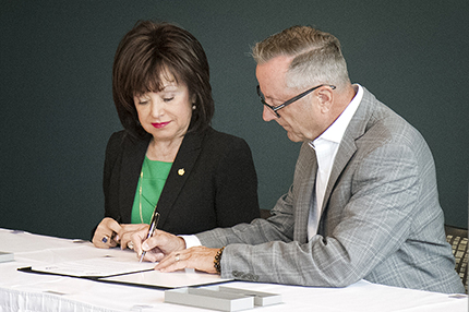 OPCMIA General President Daniel Stepano (right) signs a contract to host his organization's Instructor Training Program on the WCC campus as WCC President Dr. Rose B. Bellanca looks on.