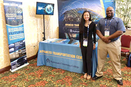 WCC students Rosa Lechartier and Zachyre Van Buren stand at the college's exhibit during the Center for Automotive Research Management Briefing Seminars in Traverse City.