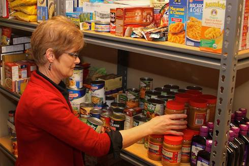 Carol Tinkle stocks the shelves of the WCC food pantry.