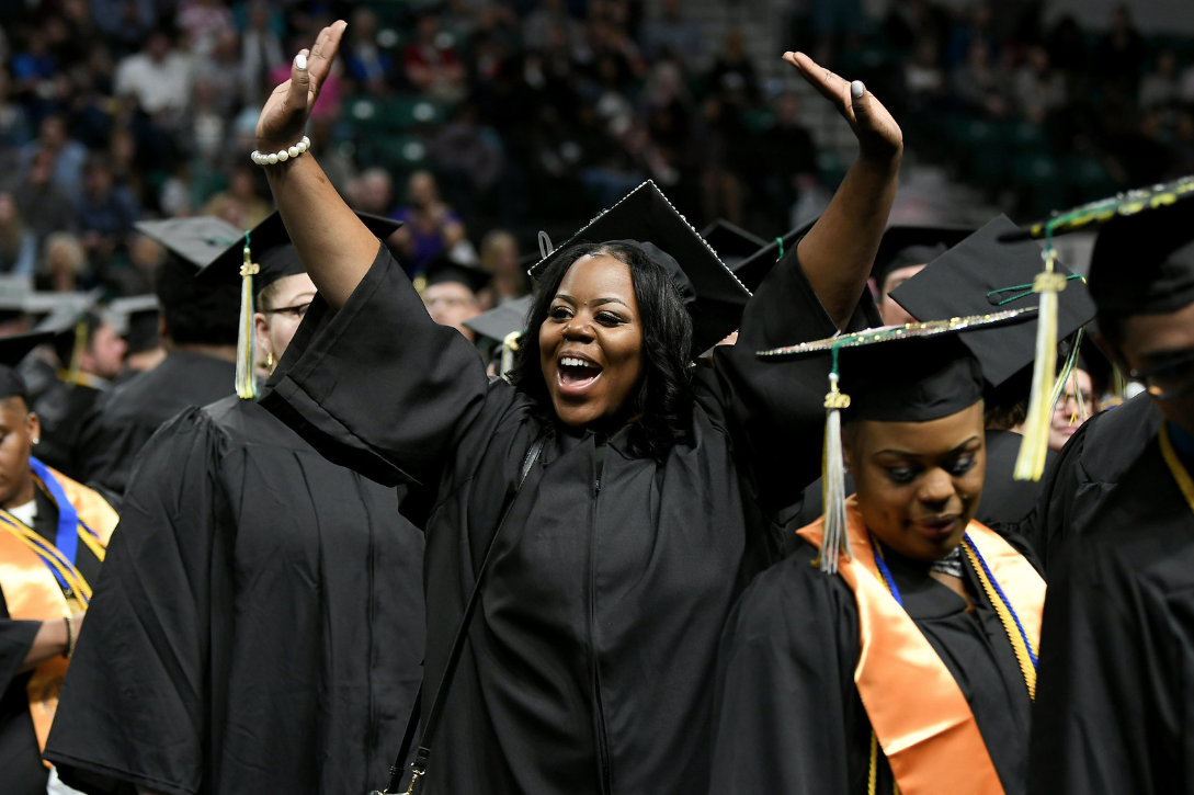WCC graduate Tanisha Harper of Detroit waves to family in the crowd prior to the commencement ceremony on May 18. (Photo by Lon Horwedel)
