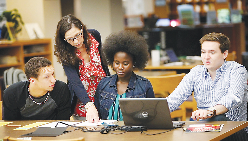 Sandy McCarthy, a librarian at Washtenaw Community College's Bailey Library, helps STEM Scholars Program participants (from left) Emijoel Lantigua, Araba Gyan and Michael Cooke with a task during one of the program's summer intensive sessions. | Photo by Kelly Gampel