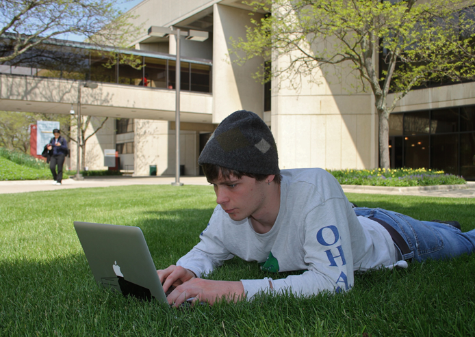 student on campus lawn with laptop